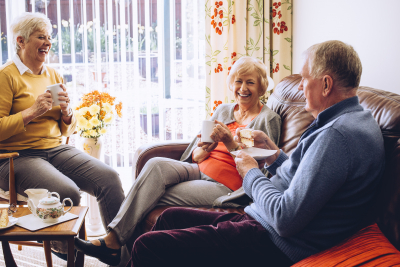 three seniors enjoying tea and cake in the care home together
