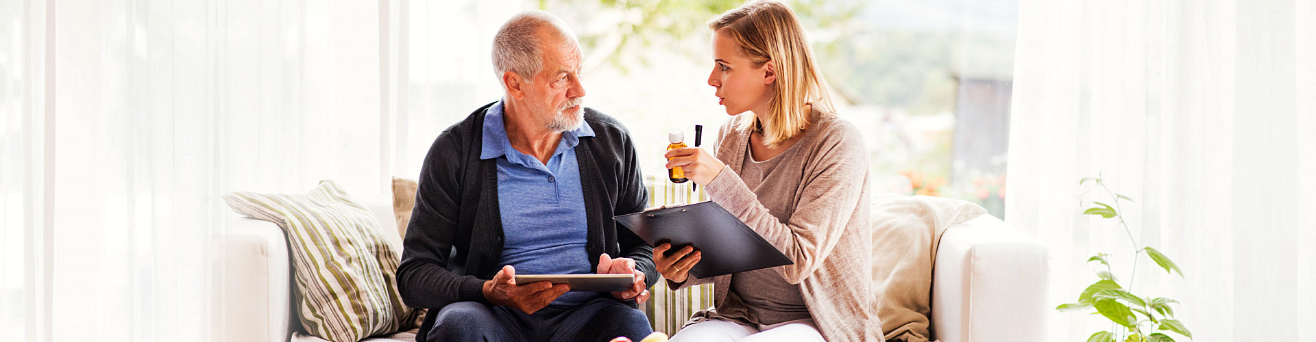 woman reminding senior of his medicine