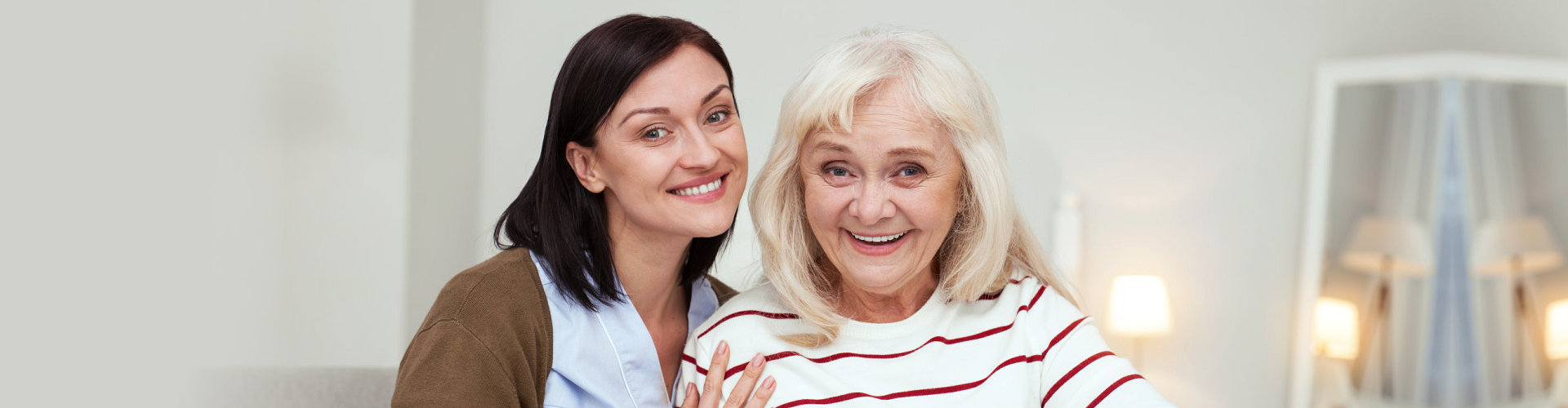 woman and senior smiling closely to each other