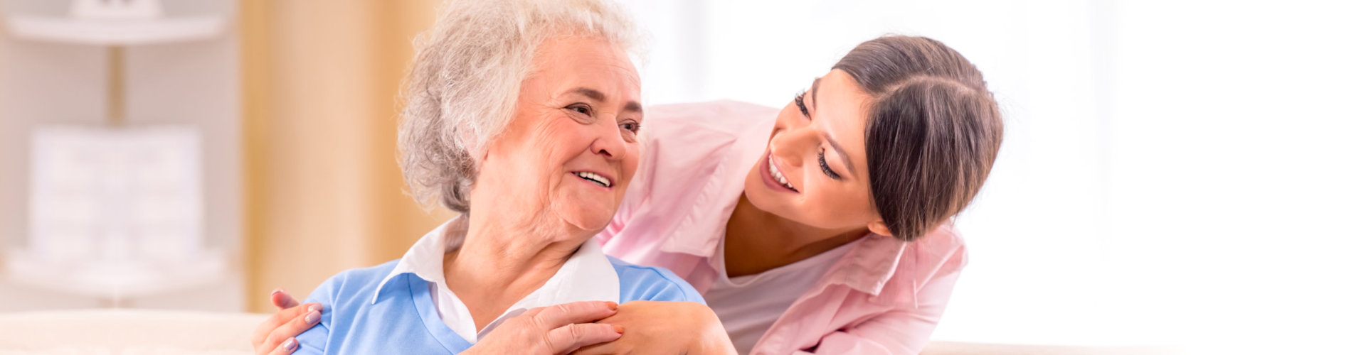 woman and senior smiling to each other